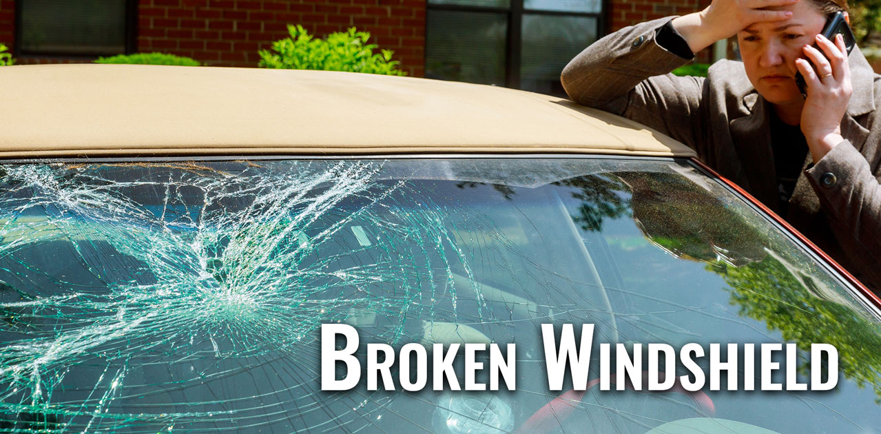 woman making a call by a broken windshield